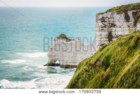 Fantastic Etretat Aval cliff, rocks and natural arch landmark near blue ocean, outdoor landscape. Above the cliff and the bay of Falaise d'Amont Etretat City, landmark of Normandy in France, Europe