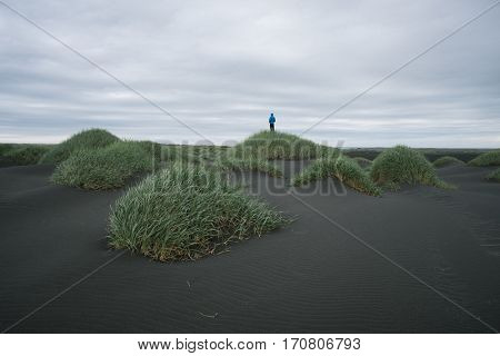 Iceland Landscape with sand dunes. Man standing on a hill. Cloudy day. Tourist Attraction near Stokksnes Cape. The muted colors, low contrast