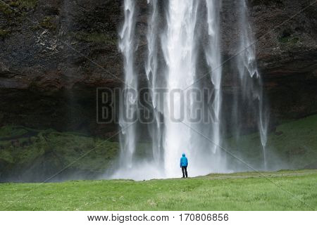 Selyalandfoss waterfall in Iceland. Tourist in blue jacket looks at the huge flow of water. Beautiful natural landmark