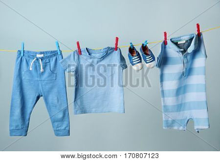 Clothesline with hanging baby clothes on grey background
