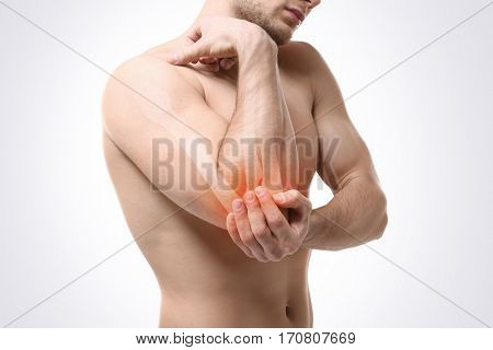 Young man suffering from elbow pain on light background. Health care concept