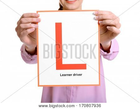 Young woman with learner driver sign on white background, closeup