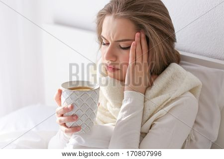 Young ill woman with cup of hot tea in bed at home