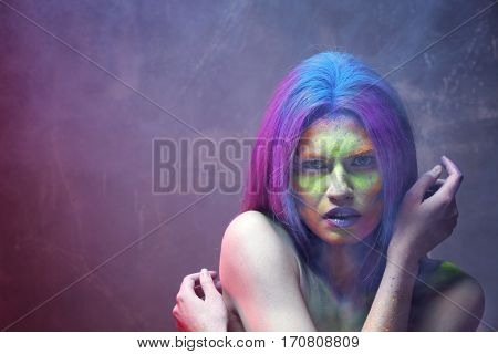 Portrait of beautiful young woman with amazing body-art on color background