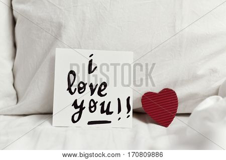 a white paper note with the text I love you written in it and a red heart placed on the white sheets of an undone bed poster