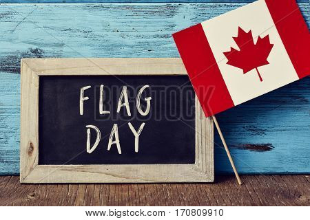 a wooden-framed chalkboard with the text Flag Day written in it and the flag of Canada placed on a rustic wooden surface