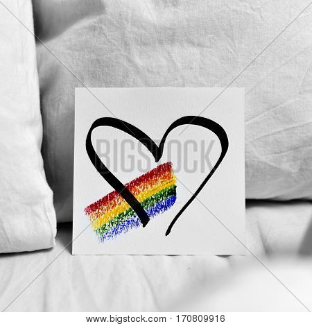 closeup of a white paper note with a rainbow and a heart drawn in it, placed on the white sheets of a bed