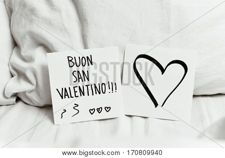 closeup of a white paper note with the text buon san valentino, happy valentines day in italian written in it, and another paper note with a heart, on the white sheets of an undone bed