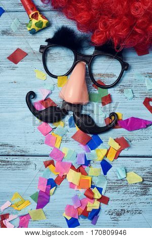 a red wig, a pair of fake black glasses with eyebrows, a nose and a mustache forming the face of a man on a blue rustic wooden surface full of confetti