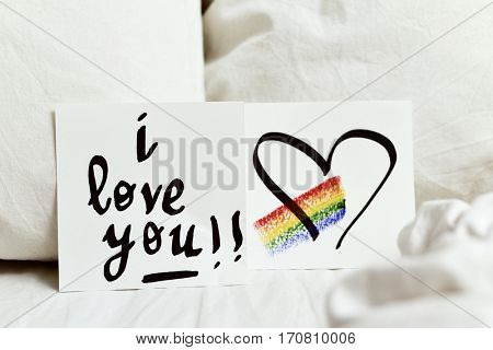 a white paper note with the text I love you and a rainbow and a heart drawn in it, placed on the white sheets of an undone bed poster