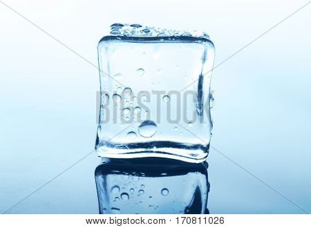Transparent ice cube with reflection on white background. Closeup of cold crystal block on clean blue glass surface with water drops