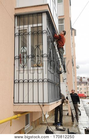 KYIV UKRAINE - February 13 2017: Contractors installing window iron security bars. Security bars for windows and balcony