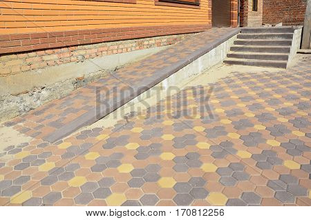 Building ramp for wheelchair entry and stairs with colorful pavers. Pavement.