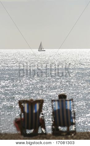 A couple on an English beach seated in deck chairs look towards a boat in focus on the horizon