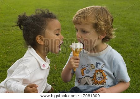 Two young children sharing an ice cream, one a blonde boy the other a mixed race girl.
