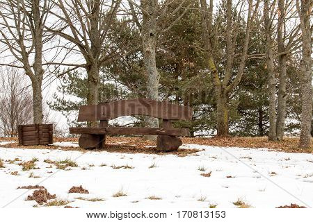 Empty wooden bench in a park at winter time