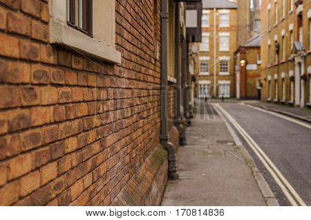 red brick wall of the building in the urban English building typical of the English historical street sidewalk street yellow painted lines gutters stone window sills