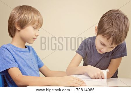 Kids reading a book. Little boy practice reading with his brother at home
