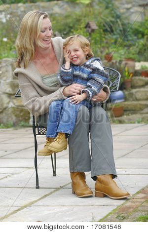 A young mother and her son laughing together seated in the garden.