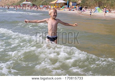 Boy Jumping In Sea Waves. Jump Accompanied By Water Splashes. Summer Sunny Day Ocean Coast
