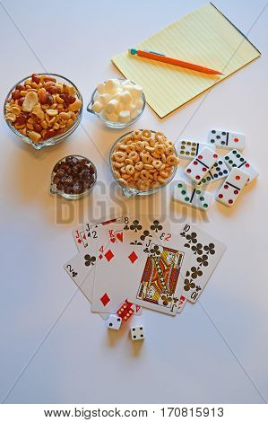 Cards dice dominoes and snacks ready for game night.