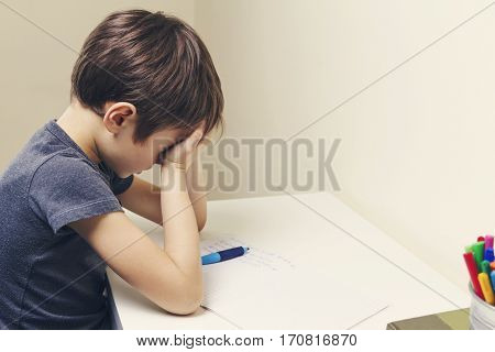 Tired child doing homework at home. The boy fed up and covers his face with hands. Education, school, learning difficulties concept
