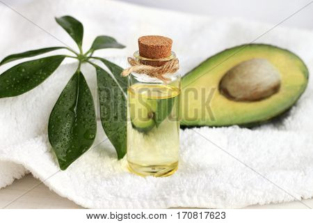 Avocado oil domestic beauty treatment use. Bottle of oil-based tonic, green plant decor on towel and fresh fruit.