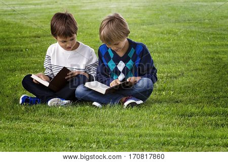 Little boys sitting on green grass in a park and reading books. Education, lifestyle, people concept