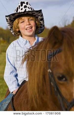 A young boy having fun riding a pony and dressed as a cowboy poster
