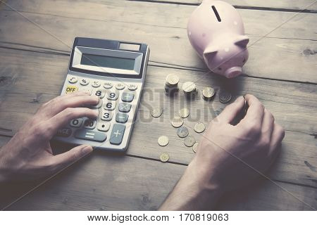 man with calculator piggy bank and coins on wooden table