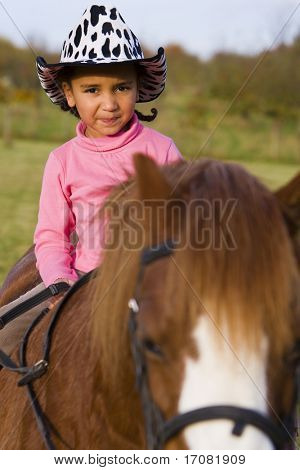 A young girl having fun riding a pony and dressed as a cowgirl poster