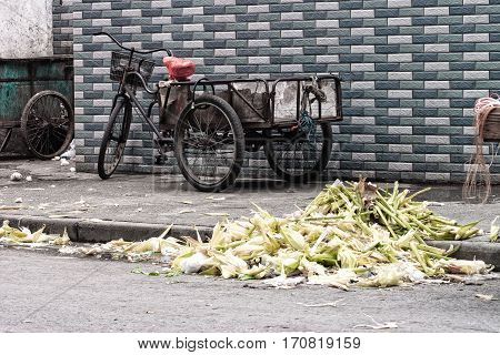 Vegetable waste on board a road old tricycle in the background