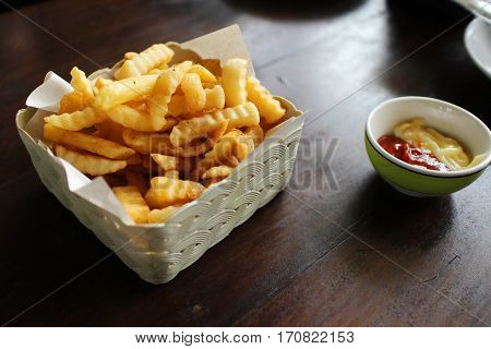 french fries with ketchup - french fried on square white basket with ketchup on the table