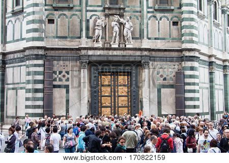 FLORENCE ITALY - APRIL 29 2016: tourists look on East doors of Baptistery (Battistero di San Giovanni Baptistery of Saint John) the doors are copy of Gates of Paradise made by Lorenzo Ghiberti