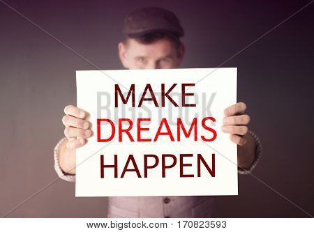stylish man holding a sign with the words Make Dreams Happen
