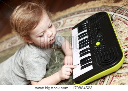Boy Lying And Playing On Synthesizer