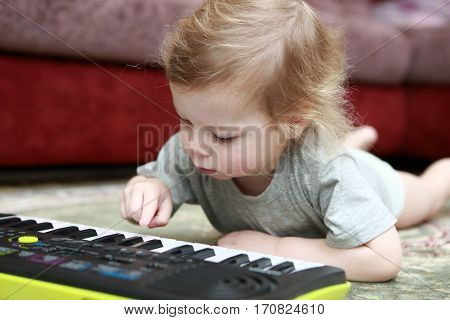 Child Lying And Playing On Synthesizer
