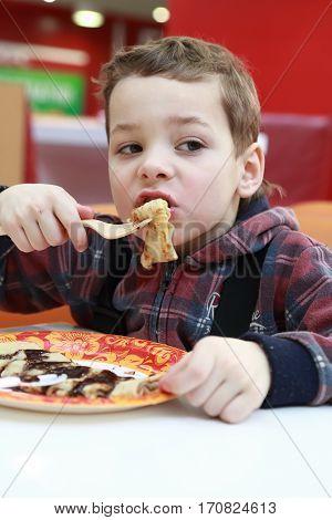 Child eating pancake at fast food court