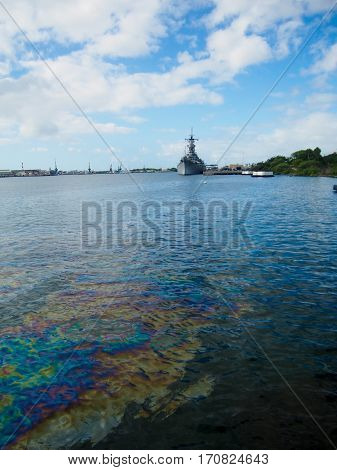 Oil still floats on the top of the water where it was spilled when the USS Arizona was sunk during the attack on Pearl Harbor Oahu Hawaii.