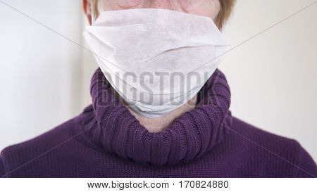 closeup of older woman with a mask protection on against the flu