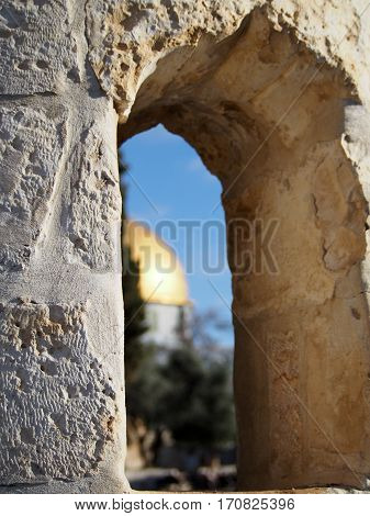 The view through a stone window in historic Jerusalem includes the iconic gold-domed mosque on the Temple Mount.