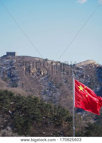 A bright red Chinese flag waves in front of the Great Wall of China.