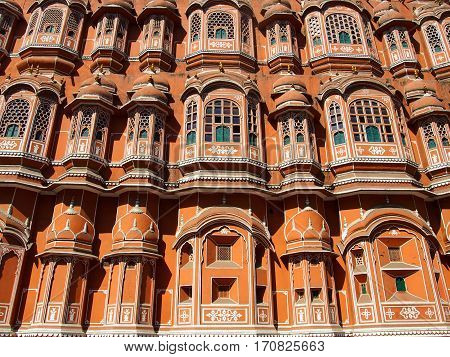 The red Palace of Winds or Hawa Mahal facade facing the streets of Jaipur India.