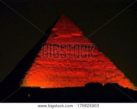 A great pyramid at Giza lit up with red light during the evening night show.