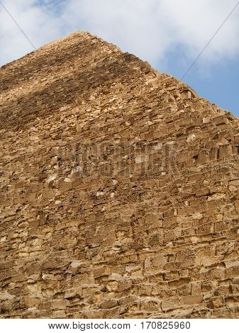 An upward view of one of the ancient pyramids of Giza in the desert outside of Cairo Egypt.