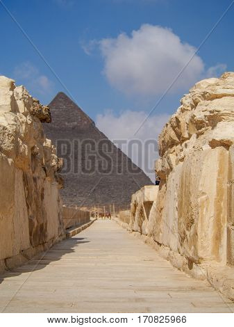 A pathway leads through ancient ruins to the Great Pyramids of Giza in the desert outside of Cairo Egypt.
