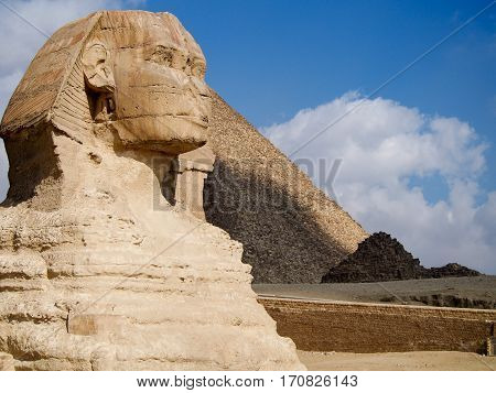 Ancient sphinx statue in front of the Great Pyramids of Giza in the desert near Cairo Egypt.