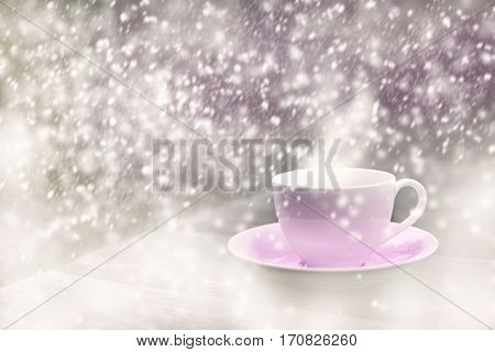 steamy pink cup on wooden table in the heavy snow