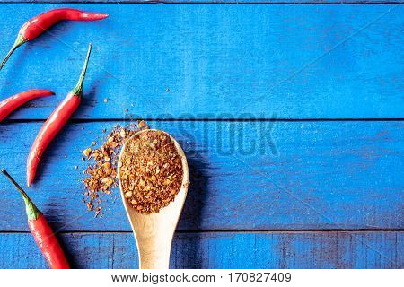 Top view of Red hot chilli peppers with cayenne on blue wooden table background Free space for text