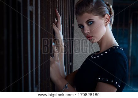 Beautiful Young Girl With A Beautiful Make-up Close-up In A Short Black Dress, Is Pressed Against Th